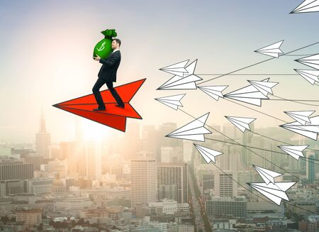 Abstract image of young businessman with money bag flying on red paper plane, leading white ones on city background. Leadership and income concept. 3D Rendering Stock Photo