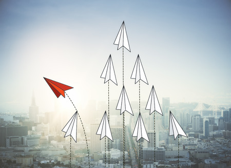 Abstract red and white paper planes flying on city background. Leadership and success concept. 3D Rendering Stock Photo