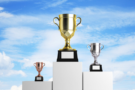 Golden, silver and bronze winners cups placed on white pedestals. Sky background. Success concept. Mock up, 3D Rendering