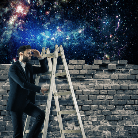 Young businessman on ladder looking at universe from behind brick wall. Adventure concept