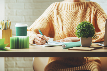 Close up of white woman working on project at wooden hipster office desk with supplies, coffee cup, books, laptop, decorative plant and other items. Workplace and lifestyle concept