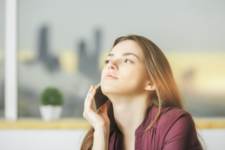 technology: Portrait of attractive young european woman talking on the phone in interior with blurry city view. Communication concept Stock Photo