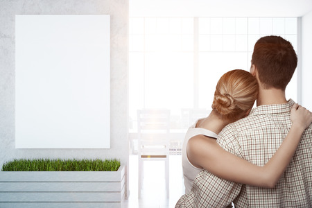 Back view of young couple cuddling in interior with city view, blank poster on concrete wall and daylight. Mock up, 3D Rendering