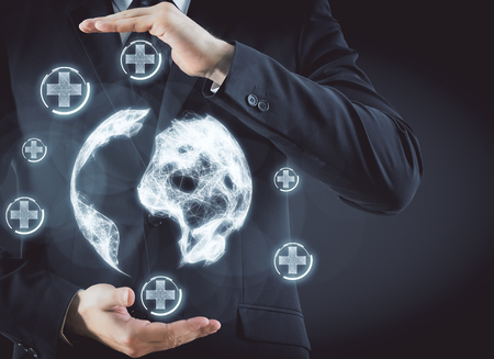 Zakenman bedrijf veelhoekige bol met abstracte gloeiende medische pictogrammen op donkere achtergrond. Geneeskunde, technologie en netwerkconcept. 3D-rendering
