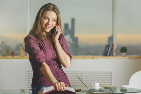 technology: Beautiful white woman sitting on glass office table with open book and talking on the phone. Blurry city view background