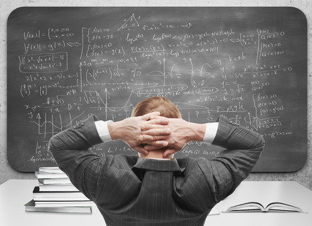 Back view of relaxing young businessman looking at chalkboard with mathematical formulas. Solution concept photo