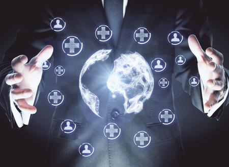Zakenman die abstracte veelhoekige bol met gloeiende medische pictogrammen op donkere achtergrond. Geneeskunde en verbinding concept. 3D-weergave Stockfoto
