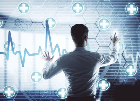 Back view of young businessman pointing at digital medical screen in blurry interior. Medicine, technology and innovation concept. Double exposure photo