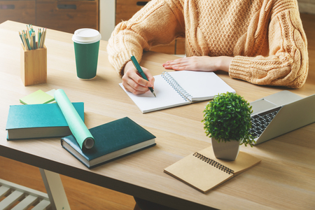 table top: Close up of caucasian woman working on project at wooden hipster office desk with supplies, coffee cup, books, laptop, decorative plant and other items. Workplace and lifestyle concept