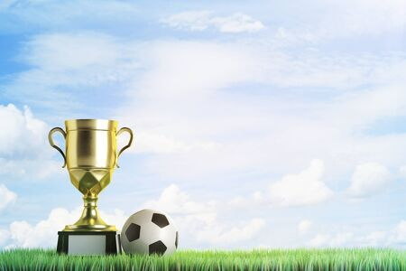 Golden winners cup with football placed on grass. Sky background with copy space. Champion concept. 3D Rendering