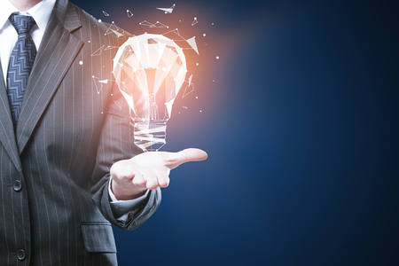Businessman holding glowing polygonal lamp on blue background with copyspace. Innovative ideas concept photo
