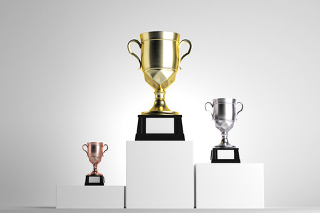 Golden, silver and bronze winners cups placed on white pedestals. Light background. Award concept. Mock up, 3D Rendering