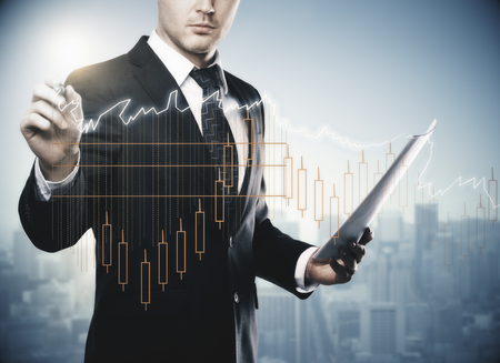 Young businessman with document in hand drawing abstract forex chart on creative city background. Finance, success, trading and income concept. Double exposure photo