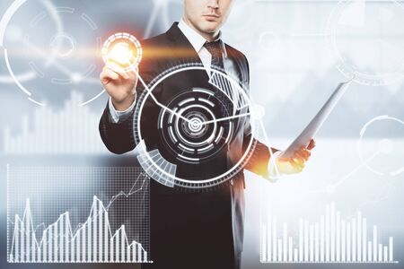 Businessman pressing abstract digital buttons on blurry gray background. Innovation, interface and touchscreen concept. Double exposure photo