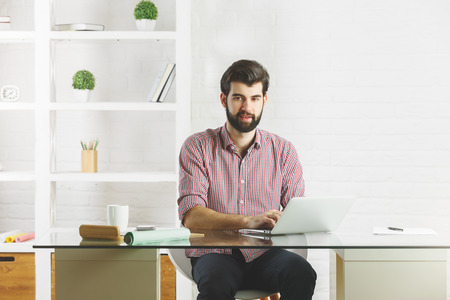 occupation: Thinking young man using laptop computer in modern office with various items on shelf. Lifestyle concept Stock Photo