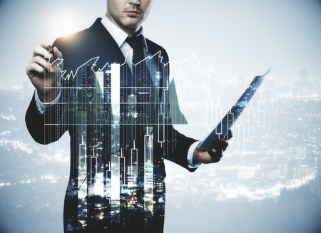 Young businessman with document in hand drawing abstract forex chart on creative city background. Finance, success, trading and analysis concept. Double exposure 스톡 콘텐츠