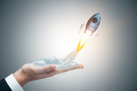 Businessman hand holding abstract launching rocket on gray background. Startup concept. 3D Rendering