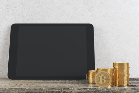 electronic commerce: Interior with empty tablet screen, golden bitcoin stacks, concrete wall and wooden floor. Accounting concept. Mock up, 3D Rendering