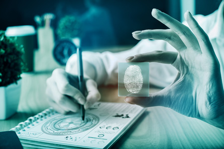 Woman at workplace holding abstract digital finger pring button. Data protection concept. Toned image
