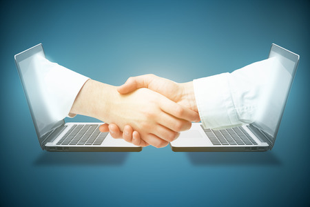Abstract image of two laptops with shaking hands on blue background. Online business concept