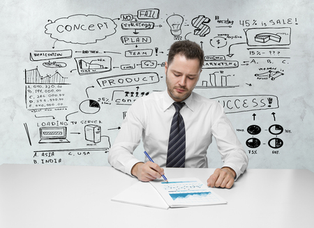 Front view of young businessman doing paperwork at white desk with business sketch in the background. Research concept photo