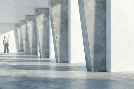 rendering: Young man drawing something in grunge concrete room interior with daylight. 3D Rendering Stock Photo