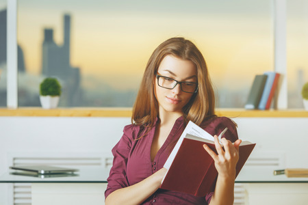 Portrait of concentrated young woman reading book in modern office with blurry city view. Education, information , student, leisure, break and knowledge concept