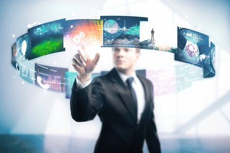 Handsome young businessman pointing at abstract colorful social media swirl in blurry interior. Multimedia concept photo