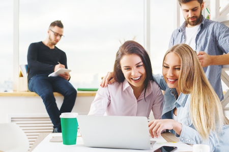 articulos oficina: Attractive young european group, business men and women working on project in modern office with laptop, smartphone, paperwork and other items on desk. Communication concept
