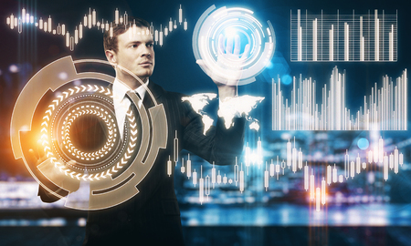 Front view of young businessman managing abstract business forex hologram on blurry night city background. Future and analytics concept. Double exposure photo