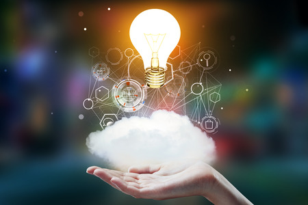 Hand holding abstract cloud with business hologram and glowing light bulb on blurry background. Idea and finance concept. 3D Rendering