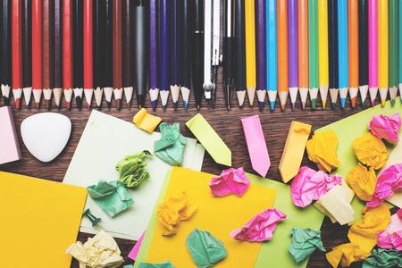 ball pens stationery: Vista superior del escritorio de la oficina de madera con bolas de papel arrugado y coloridos suministros. Concepto de papelería