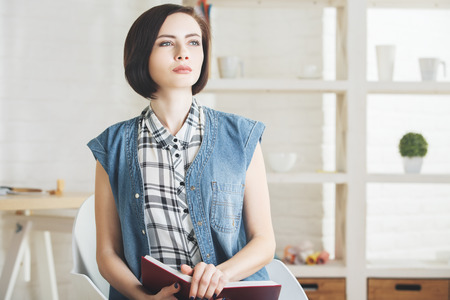 articulos oficina: Retrato del libro de lectura de la mujer bastante joven en el interior moderno de la oficina. Knoweldge, información, educación y concepto de ocio