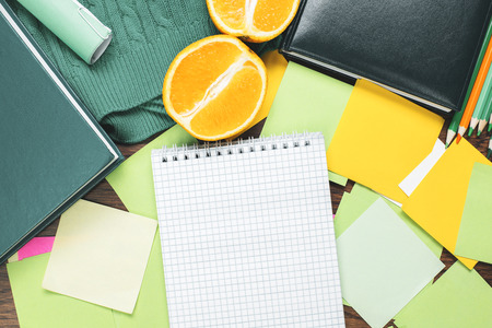 Top view of wooden desktop with empty spiral copybook, other stationery items and orange fruit halves on saucer. Workplace, office, nutrition, health and lifestyle concept. Mock up Stock Photo