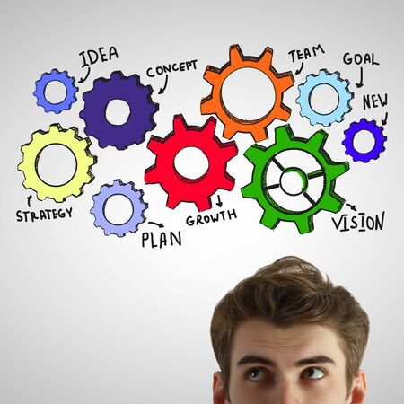 Portrait of attractive young man on light gray background with colorful cogwheels. Teamwork concept Stock Photo
