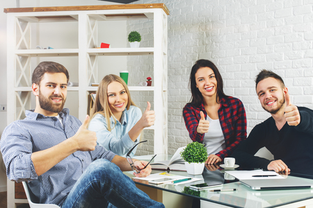 Attractive young caucasian business men and women sitting at office desk with devices, paperwork and showing thumbs up. Success concept