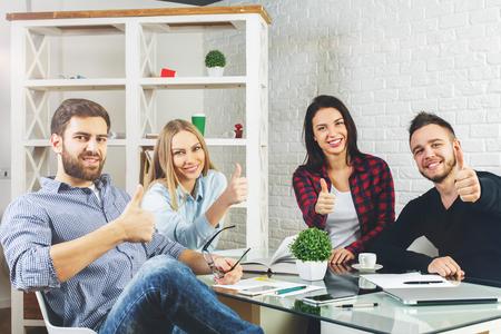 Attraktive junge kaukasische Geschäftsleute und Frauen, die am Schreibtisch mit Geräten, Schreibarbeit sitzen und sich Daumen zeigen. Erfolgskonzept Standard-Bild