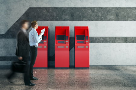 Walking businessmen in concrete interior looking at red ATM machines. Accounting and money concept. 3D Rendering photo
