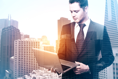 Handsome young european businessman using laptop on abstract city background. Network concept. Double exposure photo