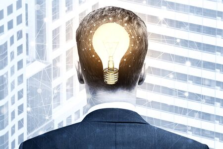 double headed: Back view of glowing lamp headed businessman on polygonal city background. Idea and innovation concept. Double exposure Stock Photo