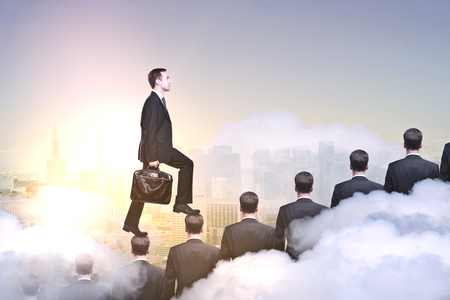 Side view of young businessman climbing people ladder on abstract city background with clouds. Leadership concept