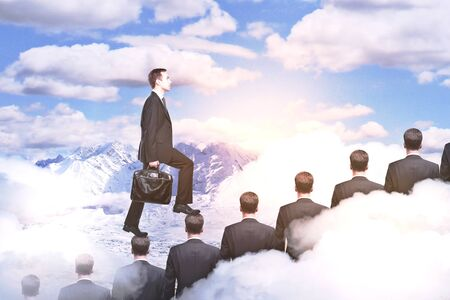 Side view of young businessman climbing people ladder on abstract mountain background with clouds. Career concept Stock Photo