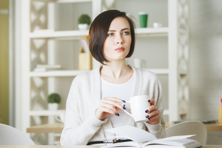 Attractive young female drinking coffee from large mug while sitting at office desktop with open book. Morning break concept