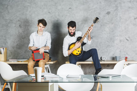 rehearse: Attractive men playing with guitar in office interior with desk and concrete wall background. Leisure, music, rehearsal, band concept
