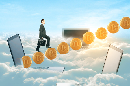 Side view of young businessman climbing abstract bitcoin ladder on bright sky with laptops background. E-business concept. 3D Rendering Фото со стока