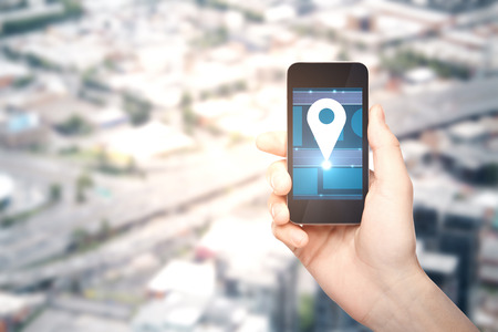 gps device: Male hand holding smartphone with location pin icon on blurry city background with copy space. Navigation concept