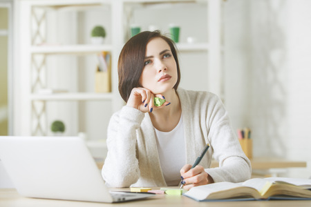 electronic book: Beautiful business woman working on project at workplace. Female secretary using laptop and doing paperwork in modern office. Occupation concept