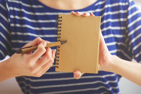 Woman in striped blue shirt holding and pointing at clean brown spiral notepad with pen. Mock up