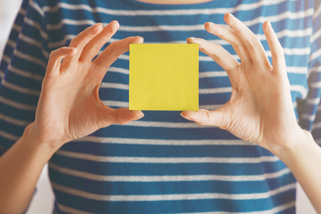 Woman in striped shirt holding empty yellow sticker. Supplies concept. Mock up