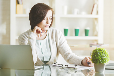 Charming business woman working on project at workplace. Female secretary using laptop and doing paperwork in modern office. Occupation concept
